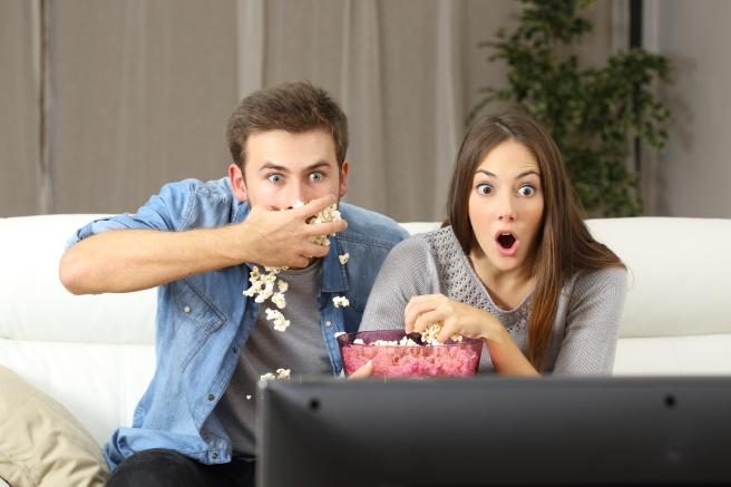 Amazed couple watching tv