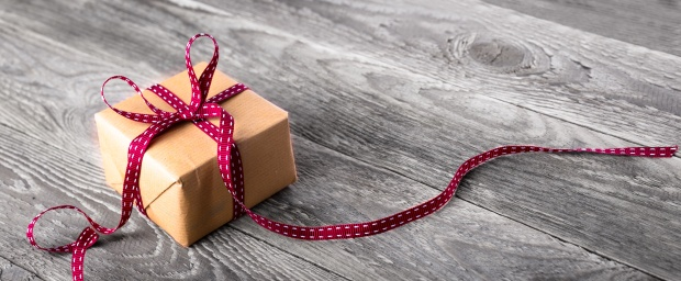 Paket mit roter Schleife auf rustikalem Holz  --  Hintergrund, Banner