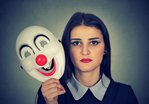 sad woman holding clown mask expressing cheerfulness happiness
